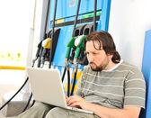 Muž s ustaraný obličej s notebookem na čerpací stanice pohonných hmot — Stock fotografie