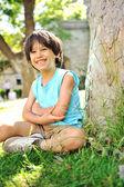 Garoto debaixo da árvore no parque — Foto Stock