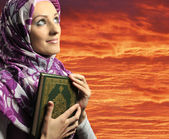 Adorable Muslim girl holding holy book Koran, against red sky — Stock Photo