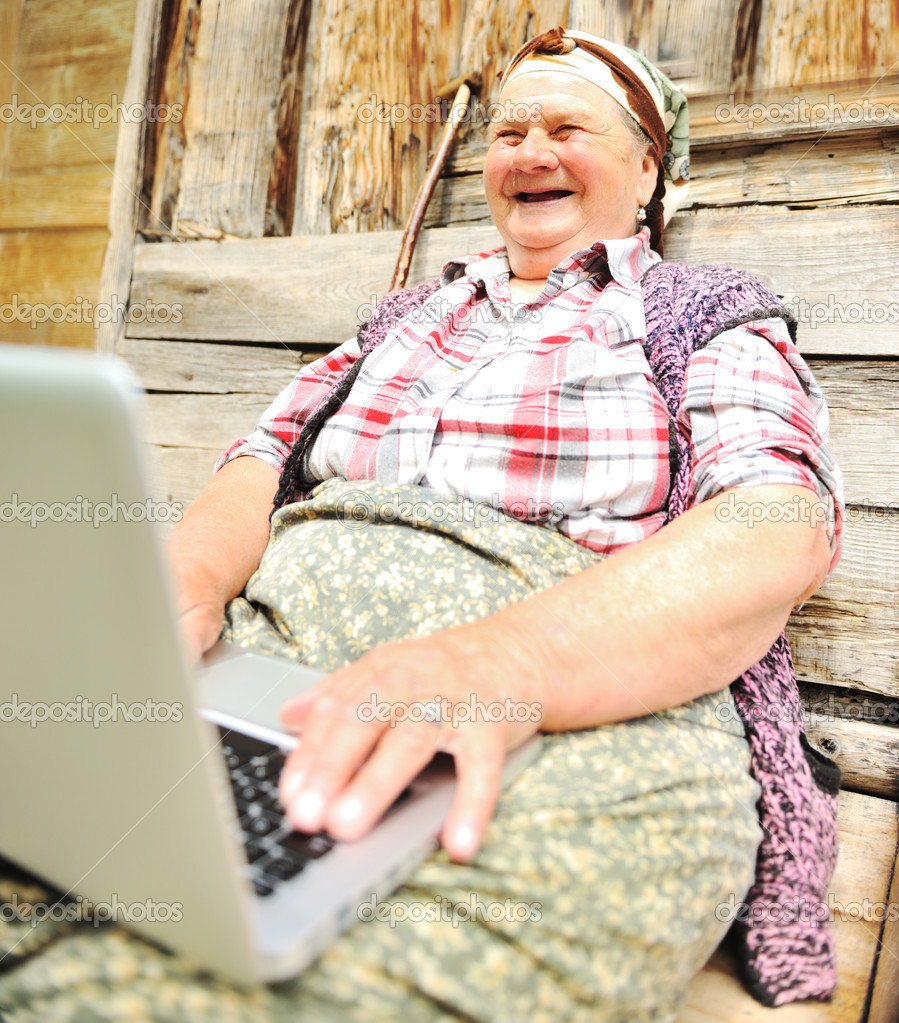 Full length of a senior woman sitting and using a laptop against — Stock Photo #6187747