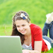 A smiling young girl with laptop outdoors — Stock Photo