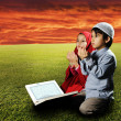 图库照片: Two Muslims children sitting on meadow in Ramadand reading Korand pra