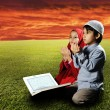 Stock Photo: Two Muslims children sitting on meadow in Ramadand reading Korand pra
