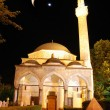 Mosque in night with crescent and star above - Stock Photo