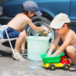 Two children wathing car and toy car - Stock Photo