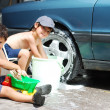 Playing around the car and cleaning, children in summertime — Stock Photo