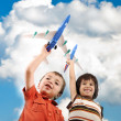 Two small boys with airplains in hands, idea for traveling around the World — Stock Photo
