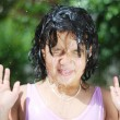 Splashing water in summer, cute girl playing outdoor in nature - Stockfoto