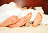 Lovely couple in bed, focus on feet — Stockfoto
