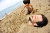 Playing with sand and digging the father in — Stock Photo