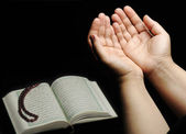 Hands up, islamic praying, Koran beside — Stock Photo