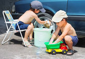 Two children wathing car and toy car — Stock Photo