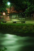 Lamp and bench in night — Stock Photo
