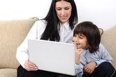 Matka i syn z notebooka na kanapie razem — Zdjęcie stockowe