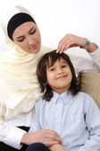 Muslim arabic covered mother and son relaxing at the home — Stock Photo