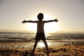 Silhouette of child on the beach, holding his hands up, towards the sun — Stock Photo