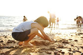 Kid on beach in sand playing, around, summer hot nice time — Stockfoto