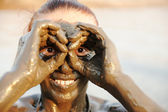 An elderly woman enjoying the natural mineral mud on face sourced from the — Stock Photo