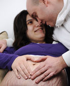Hearth shape on pregnant's belly, couple in love — Stock Photo
