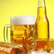 Glass of beer with foam on yellow background — Stock fotografie
