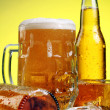 Glass of beer with foam on yellow background - Stock Photo