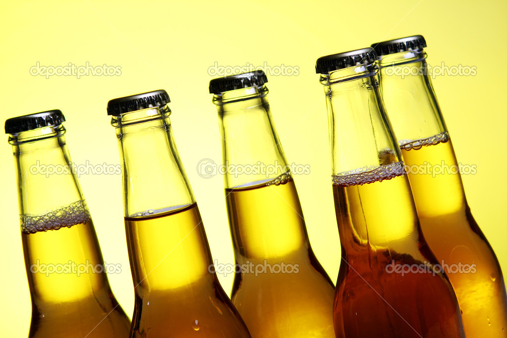 Ottles of cold and fresh beer with ice over yellow background  Stock Photo #5716669