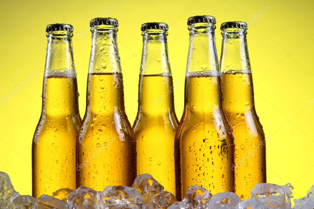 Bottles and Glass of beer with foam over yellow background — Stock Photo #5716694