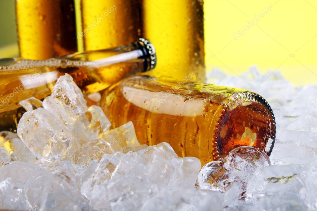 Bottles of cold and fresh beer with ice over yellow background — Stock Photo #5716700