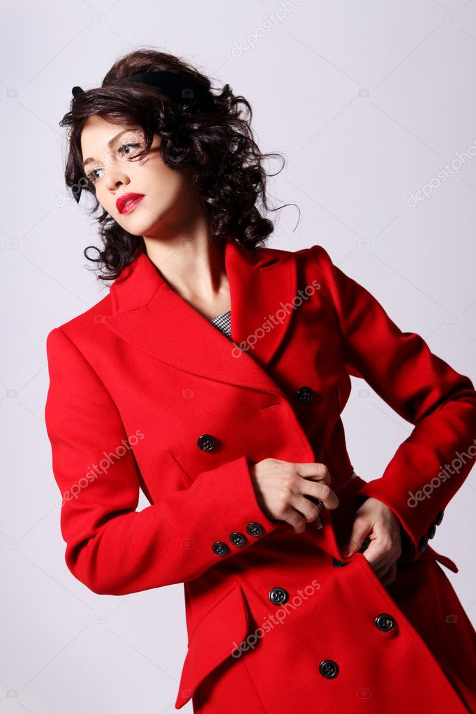 Beautiful young woman in red coat posing on white background — Stock Photo #5841828