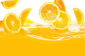 Fresh oranges falling in juice — Stock Photo