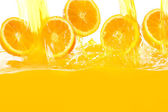 Fresh oranges falling in juice — Stok fotoğraf