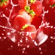 Strawberry falling into the lot of juice — Stock Photo #6258570