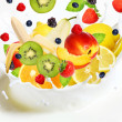 Lot of different fruits falling into milk — Stock Photo