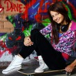 Beautiful teenager girl with headphones sitting on skateboard — Stock Photo
