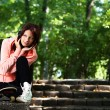 Beautiful teenager girl with headphones in the park — Stock Photo