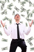 Happy businessman and flying dollar banknotes — Stock Photo