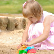 Cute girl playing on sand - Stock Photo