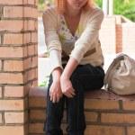 Woman sitting on brick wall — Stock Photo #5422647