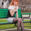 Ginger-haired woman sitting on bench and eating icecream cone — Stock Photo