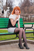 Ginger-haired woman sitting on bench and eating icecream cone — Foto de Stock