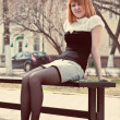Ginger-haired woman sitting on a bench — Stock Photo