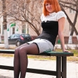 Ginger-haired woman sitting on a bench — Stock Photo #5607520