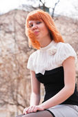 Beautiful young ginger-haired woman putting out her tongue — Stock Photo