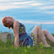 Beautiful ginger-haired woman sitting on the ground — Stock Photo
