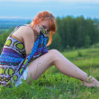 Beautiful ginger-haired woman sitting on the ground — Stock Photo #6035022