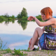 Beautiful ginger-haired woman at the coast of pond — Stock Photo