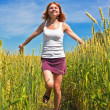 Beautiful young woman running through a wheat field — Stock Photo