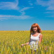 Beautiful young woman walking at wheat field — Stock Photo