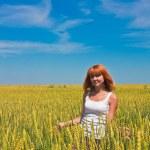 Beautiful young woman walking at wheat field — Stock Photo