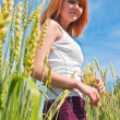 Beautiful young woman walking at wheat field — Stock Photo #6284090